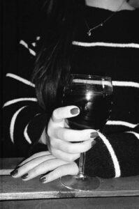 Greyscale photo of alcoholic holding glass of wine
