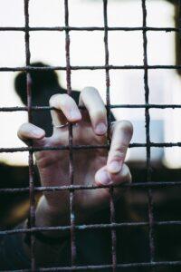 Prisoner holding onto black metal fence
